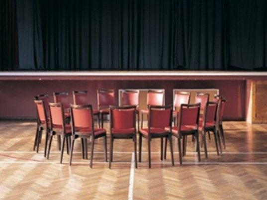Image of Mary McIntyre's: Aura of Crisis 1998. The photograph shows a ring of empty leather backed chairs arranged in an empty hall.