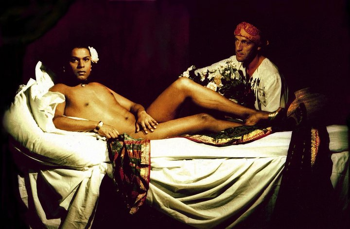 Image of George Chakravarthi's: Olympia, 2003, a man in repose being attended to by another man with a bouquet of flowers