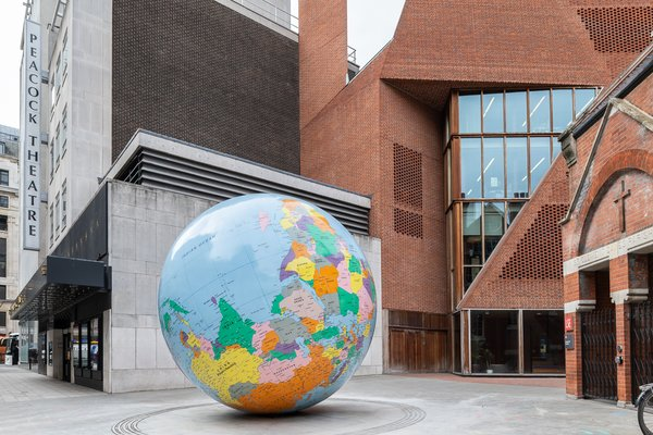 Image of Mark Mark Wallinger's: The World Turned Upside Down. A large coloured globe is positioned in front of a modern brick building.
