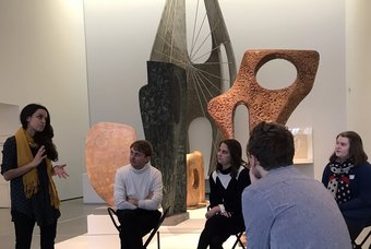 A group of people sitting amongst artworks on gallery
