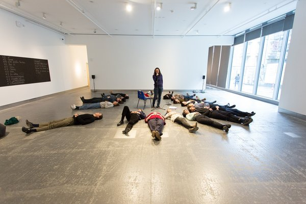 Image of people lying down in a circle around a standing woman