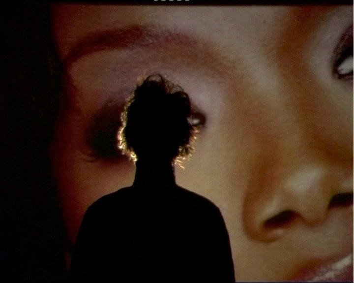 Image of Mark Leckey's: Parade, 2003. A man is silhouetted against a larger photograph of a woman's face.