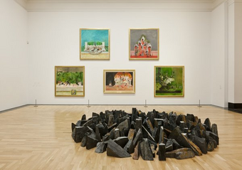 Image of a gallery within the National Museum in Cardiff. A collection of stones have been collected into a circle, in front of a collection of paintings.