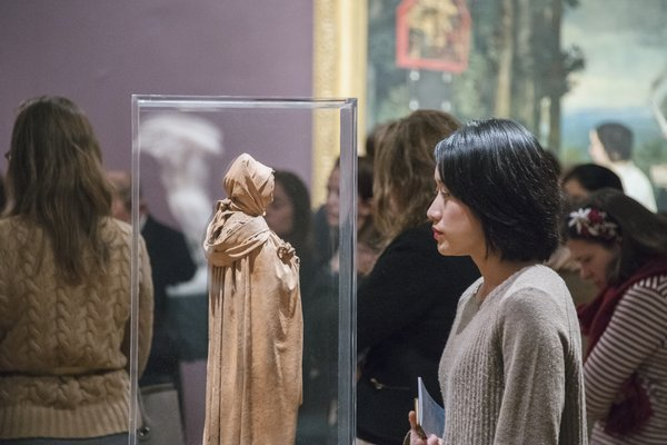 Image of attendees to Tate Patron's event. A woman is looking at a small model of a hooded statue.