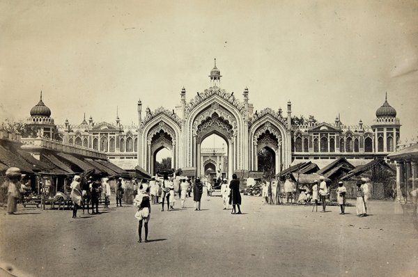 Sepia photograph of colonial India; people are standing in front of a palace gate.