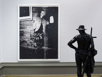 Image of Wolfgang's Tillmans' Installation at Walker Art Gallery in 2010. A statue of a topless man holding a scythe facing away from camera, and a large grainy photograph of another man.