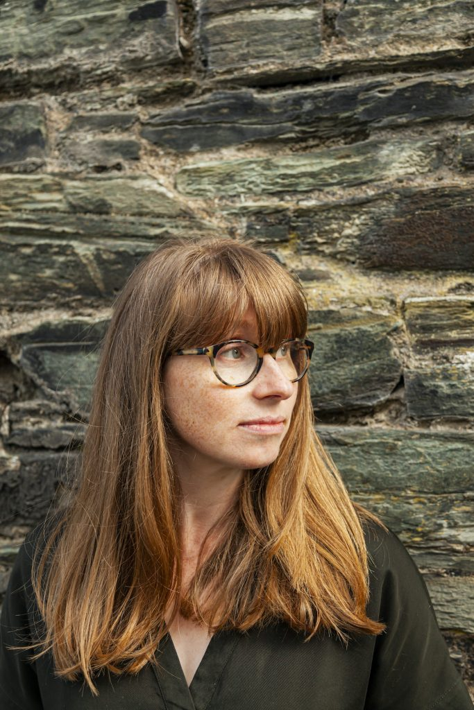 Catherine Hemelryk, standing in front of a brick wall, looking to her left.