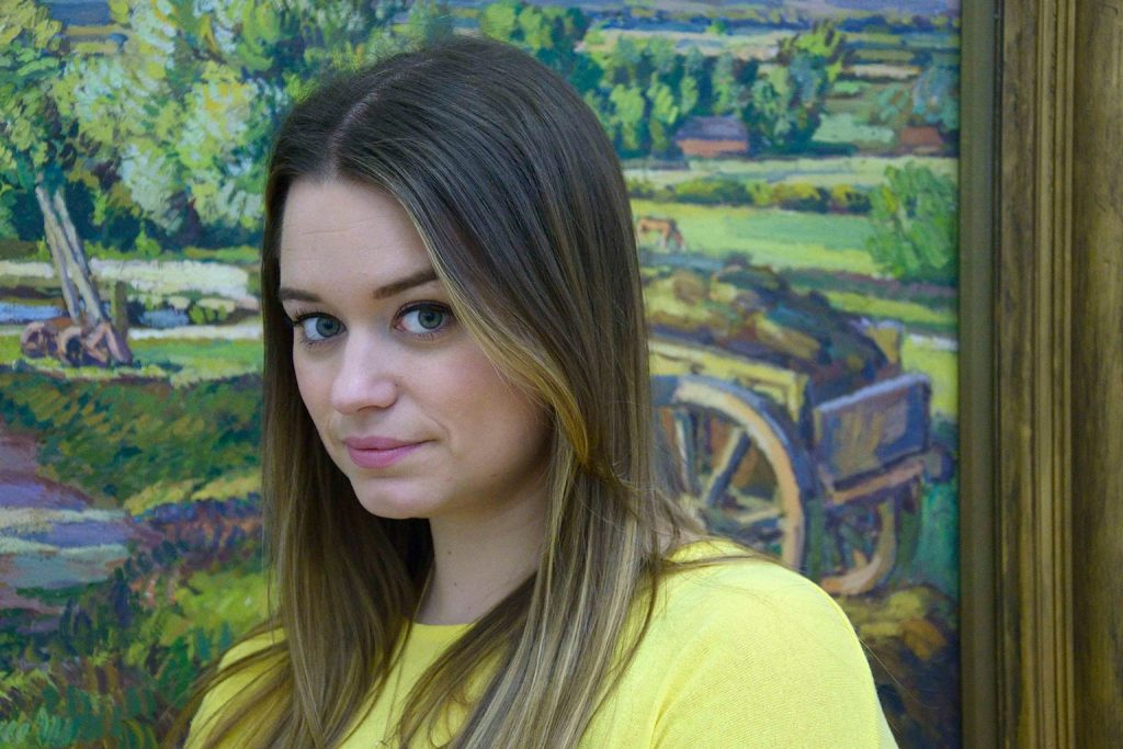 A photograph of Charlotte Kennan, standing in front of a pastoral painting, looking directly to camera.