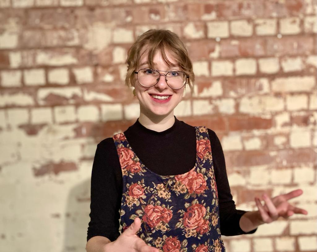 A photograph of Marta Marsicka standing in front of a brick wall, smiling and looking directly onto camera.