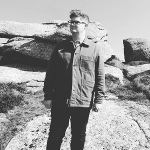 A black and white photograph of Matt Retallick standing in front of granite rocks.