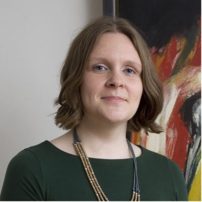 A photograph of Sophie Hatchwell standing in front of a painting, she is looking direclty into camera.